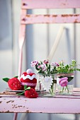 Fruits and cakes hand-crafted from scraps of felt, red socks and jersey next to preserving jars decorated with heart and fabric rose