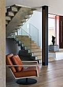 Leather armchair with modern, metal frame in open-plan stairwell with entrance area and black metal pillar in front of stone staircase with glass balustrade
