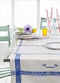 Blau-weisse Geschirrtücher als Tischdecke, Tellerstapel mit Anemonen und Flaschen auf rustikalem Küchentisch