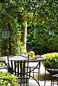 Refreshing drinks on metal garden table with matching chairs and lanterns hanging from tree in sunny garden