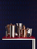 Pots and vessels made from traditional copper and modern stainless steel on Bordeaux red side table against midnight blue background