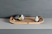 Grey lemon and pear sculptures on wooden tray against grey-painted background