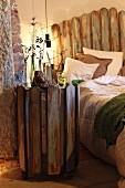 Beistelltisch aus recycelten Holzlatten und Doppelbett mit Lattenzaun als Bettkopfteil
