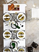Top view of place settings with white linen napkins and dish of appetisers on white table cloth with runners