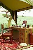Arbeitsplatz im Kolonialstil unter einem Zeltdach vor steppenartiger Landschaft