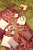 Cushions and plates of food on ethnic picnic blanket in meadow