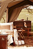 Elegant sleeping area with colonial-style chest of drawers below tent roof and view of landscape
