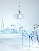 Insubstantial - glass containers on transparent table and plexiglass chair below pendant lamp with segmented lampshade