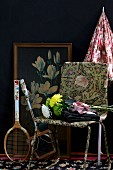 Bouquet on retro chair and tennis racquets in front of framed picture leaning on black-painted wall