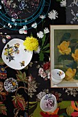 Top view of cups, plates, yellow flowers and framed picture on floral fabrics