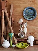 Small china table lamp with figurine of woman, painted plate and sculpture of child's head; turned wooden table legs leaning in corner