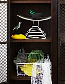 Metal ornaments - bird cage, wire duck and bird figurine on yellow stone in old locker with wire mesh door