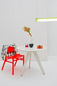 Modern dining set for one with bright red chair and small, three-legged table below purist strip light