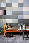 Graphic wall design of rectangles in shades of grey combined with colour-coordinated standard lamp, side table and couch