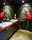 Moderne Waschtischzeile und als Handtuchhalter verwendetes, an die Wand gehängtes Fahrrad in dunkel getöntem Badezimmer