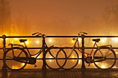 Bicycles against bridge balustrade in front of illuminated canal (Amsterdam)