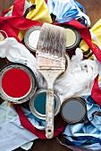 Still-life of paintbrushes, paint pots, fabrics & ribbons
