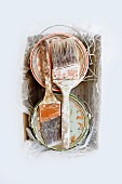 Two paint pots and two paintbrushes in cardboard box (top view)