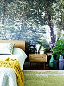Photo wallpaper with forest motif in bedroom; matching accessories such as plant arrangements and floral print pillows