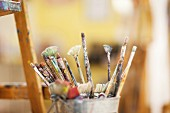 Different paintbrushes in container next to easel (close-up)