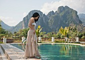 Woman dipping foot in water of swimming pool (Vang Vieng, Laos)