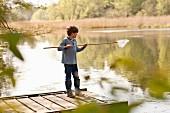 Junge steht mit Kescher auf Bootsteg am See
