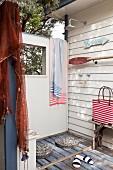 Aussendusche an holzvertäfelter Wand mit umfunktioniertem Holzpaddel und maritimem Streifendessin auf Badetasche und Handtüchern