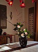 Oriental-style living area with Chinese wall hangings and flower arrangement in black lacquer vase