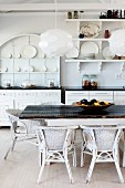 Modern pendant lamps above rustic table and white rattan chairs in front of kitchen counter and white crockery on wall-mounted shelves