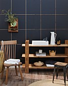 Bathroom utensils on simple, plain wood shelves against dark blue tiles wall with wooden chair and stool in foreground