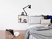 White wooden crate mounted on wall and painted white inside with ornaments and clip lamp used as bedside cabinet next to unmade bed and laundry basket