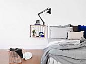 Innen weiss gestrichene Holzkiste mit Klemmleuchte und Deko als Nachttisch an die Wand gehängt, daneben ungemachtes Bett und Wäschekorb