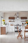 White fitted kitchen with wooden accents on doors and folding chairs at breakfast tables