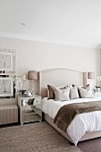 Bedroom in shades of beige with scatter cushions and fluffy blanket on double bed and bedside cabinet with mirrored drawers
