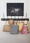 Striped bags and summer hats hanging on vintage coat rack below oil painting of cows