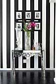 Verchromter Metalltisch mit verschiedenen Blumenvasen vor Wand mit schwarz-weissen Streifen und gerahmter Photogalerie