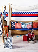 Beach atmosphere - pouffes and anchor ornament in front of wicker bench with various cushions below canopy and in front of wave motif painted on wall