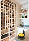 Modern kitchen with large wine rack in fitted shelving; bowl of lemons on counter