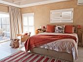 Mediterranes Schlafzimmer mit Doppelbett unter Fenster mit geschlossenen Innenläden und bodenlanger Vorhang an Terrassentür