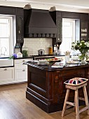 Union Flag cushion on bar stool at solid wood counter in open-plan, country-style kitchen