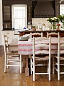 Tablecloth on rustic table and wooden, rush-bottom chairs in country-style kitchen