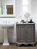 Pedestal washbasin and toiletries on vintage-style, half-height cabinet in traditional bathroom