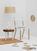 Wooden chair with white seat and backrest next to vintage-effect side table and decorative letters on floor