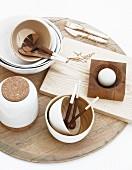 Holz Besteck in Bambusschale mit weisser Aussenlackierung neben Schneidebrett und Porzellanbehälter auf Vintage Holzscheibe