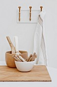 Kitchen utensils in white and wooden bowls and chopping board on table in front of tea towel hanging from hook rack