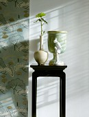 Flower in vase on black-painted plant stand next to strip of wallpaper with stylised pattern