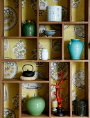 Small ornaments in backless display case against wallpaper with crockery motif