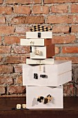 Stacked, white boxes with attached gaming pieces and dice against rustic brick wall