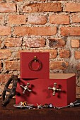 Stacked, rust red boxes with attached components against rustic brick wall