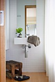 Bathroom with white tiles, sink, mirror and wooden stool